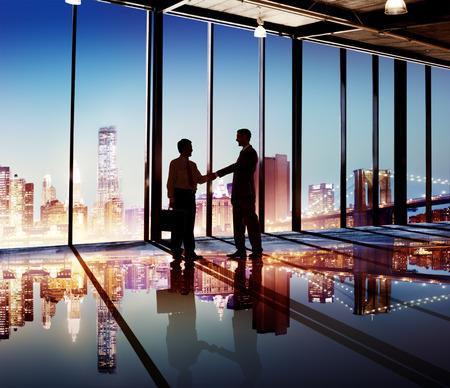 projectontwikkelaars die elkaar de hand schudden met uitzicht op een skyline